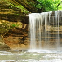 A visitor photographs one of the many waterfalls at Starved Rock. Photo courtesy of Starved Rock State Park.