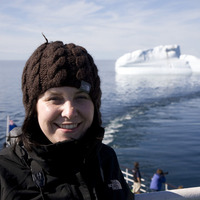 Writer Amy Watkins posing with an iceberg behind her, photo by Geraint James